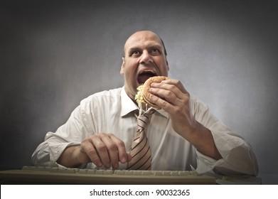 Fat businessman eating a hamburger while using a computer