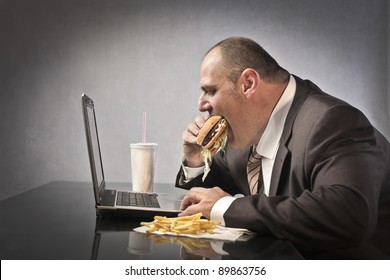 Fat businessman eating junk food while working