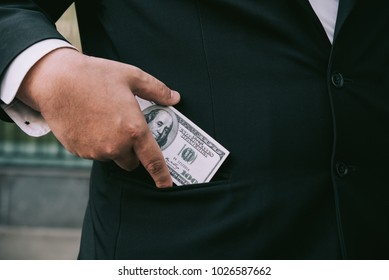 Fat Businessman putting money in his pocket.
