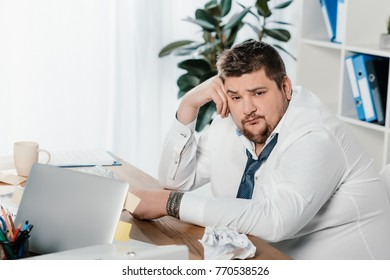 fat businessman sitting at workplace with crumpled papers and laptop