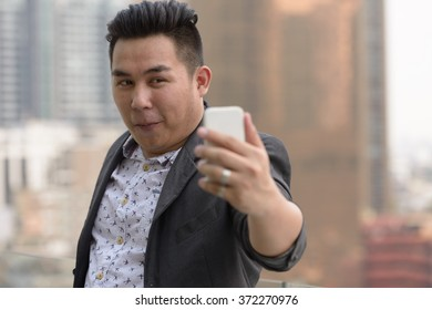 Fat businessman using mobile phone
