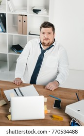 fat businessman working with notepad and laptop in office
