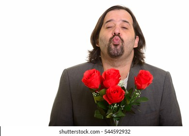 Fat Caucasian businessman puckering lips while holding red roses ready for Valentine's day isolated against white background