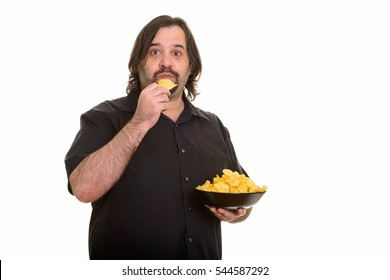 Fat Caucasian man eating bowl of chips isolated against white background