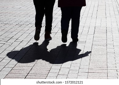 Fat couple walking down the street, silhouettes and shadows on pavement. Two women on a sidewalk, concept of overweight, female friendship