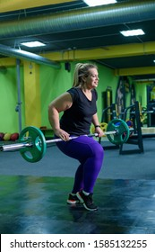 Fat European woman is engaged in fitness with a barbell in the gym. A fat girl does deadlift.