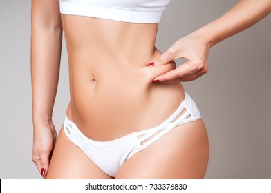 Fat female belly, woman holding her skin for cellulite check. Getting rid of belly fat and weight loss