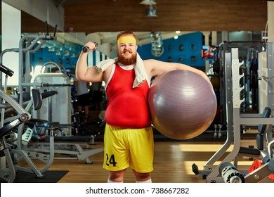 Fat funny man with dumbbells in the gym.