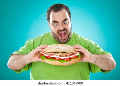 fat funny man eat a huge sandwich isolated on blue