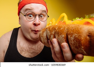 Fat funny man eating unhealthy big burger