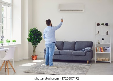 Fat funny man holding an air conditioning control panel while standing at home.