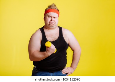 Fat funny man try to lift small yellow dambbell
