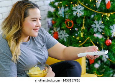 Fat girl is eating potatoes chips and watching TV in her house during Christmas time with concept relaxation at home during Christmas holiday.