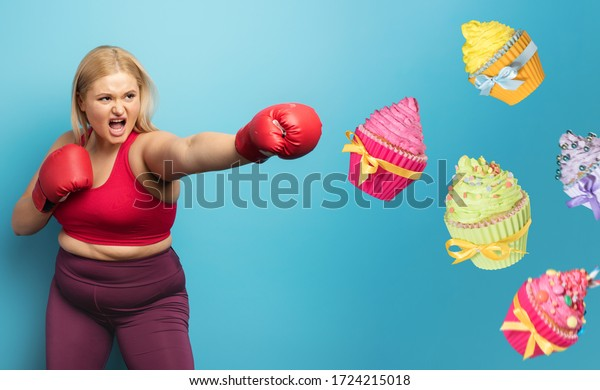 Fat girl in fitness suite does boxing and fight against cupcakes. Cyan background