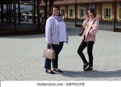 a fat girl and a thin slender blonde on a walk in the city. A bright and spring shot with cheerful girlfriends in spring clothes. Female students in the yard with geometric wooden structures