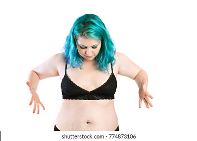 Fat girl. Upset overweight young woman looking at her fat midriff, abdomen. Pot belly