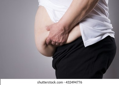 Fat human body. Thick belly closeup on gray background