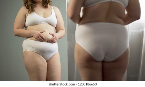 Fat lady looking at belly reflection, wants to lose excess weight, diabetes risk