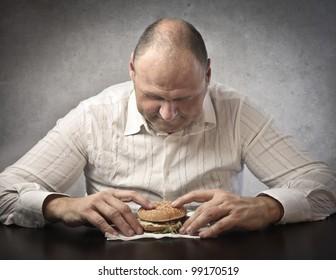 Fat man about to eat a hamburger