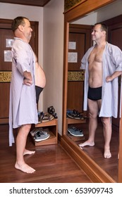 Fat man in a bathrobe sees in the mirror slim body. The mirror improves the figure of the man. The self-deceit of older man when look at himself to mirror. Male beauty.