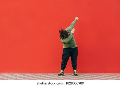 Fat man in casual clothes stands on a red background and dances a dab dance. Overweight guy shows dab movement in dance on red wall background.