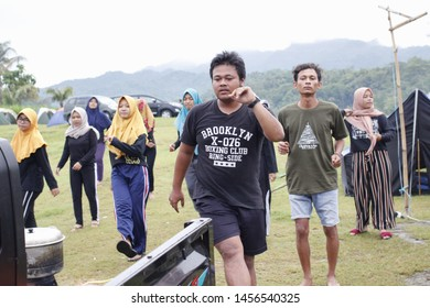 The Fat man as dance leader guiding  to the other. They are look happy and enjoy the dance on the morning at Waduk Sermo Yogyakarta on December 2019