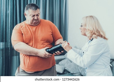 Fat Man with Doctor in White Coat With Cola. Woman in White Coat. Diet and Healthcare Concept. Man with Bulimia. Unhealthy Lifestyle Concept. Man with Overweight. Patient with Bottle.