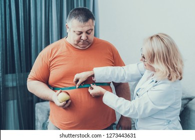 Fat Man with Doctor in White Coat in Gray Room. Woman with Tailors Centimeter. Diet and Healthcare Concept. Man with Bulimia. Unhealthy Lifestyle Concept. Man with Overweight. Patient with Stomach.