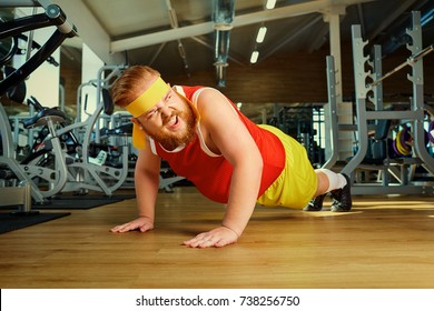 A fat man does push-ups from the floor in the gym.