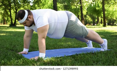 Fat man doing plank, training outdoors, desire to be slim, motivation willpower