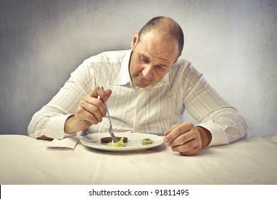 Fat man with doubtful expression examining the food in his dish