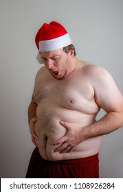 Fat man dressed as a naked santa grabbing his belly