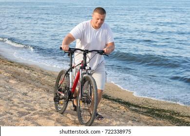 A fat man drives a bicycle along the seashore