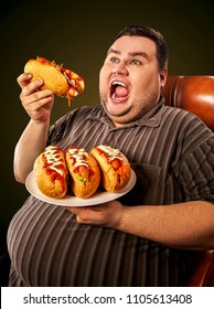 Fat man eating fast food hot dog on plate. Breakfast for overweight person. Junk meal leads to obesity. Person regularly overeats concept on black background. Man after hunger strike.