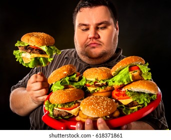 Fat man eating fast food hamberger. Breakfast for overweight person. Junk meal leads to obesity. Person regularly overeats concept on black background.
