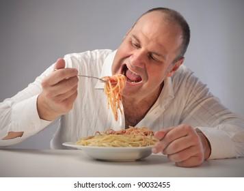 Fat man eating spaghetti