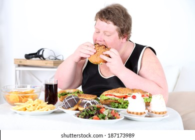 Fat man eating a lot of unhealthy food, on home interior background