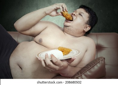 Fat man eats fast food while sitting on sofa at home