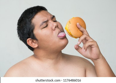 a fat man eats unhealthy food, junk food or fast food is bad for our health concept, he is holding hamburger and eat it