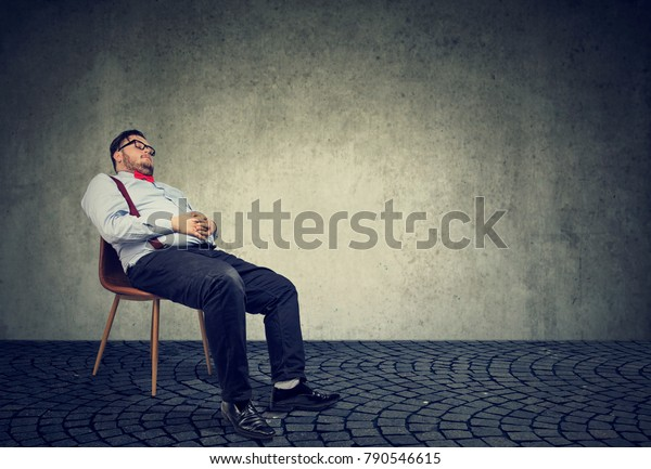 Fat man in formal clothing sitting on chair and sleeping in dream.