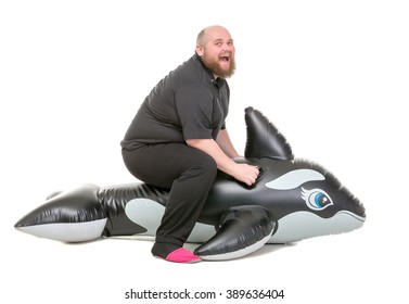 Fat Man Fun Jumping on an Inflatable Dolphin, isolated on white background