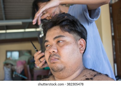 Fat Man getting a haircut by a hairdresser at his house.