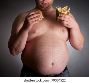 Fat man with hamburger and chips on dark background