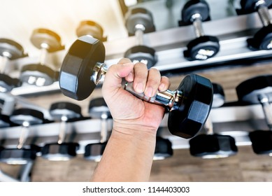 fat man Hand holding  black metal dumbbells in the gym