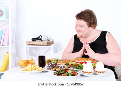 Fat man has a big lunch, on home interior background