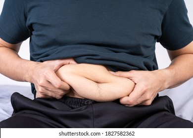 Fat man holding excessive fat belly, overweight fatty belly. Diet lifestyle, weight loss, stomach muscle, healthy concept.
