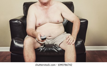 Fat man holding a remote control while watching tv