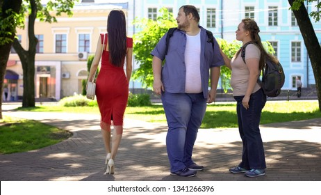 Fat man looking at beautiful lady in red passing by, obese girlfriend jealous
