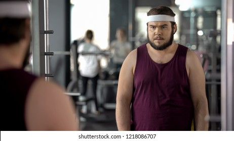 Fat man looking at mirror reflection in gym, mental training before workout