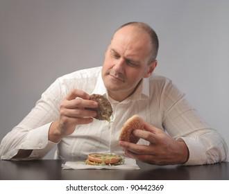 Fat man observing the contents of a hamburger